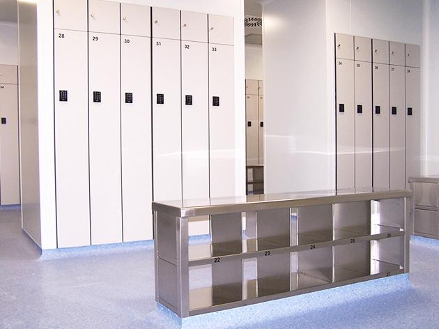 Vestuario para laboratorios con taquillas y bancos de paso en acero inoxidable.